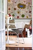 Blick durch offene Tür auf Metall Drahtstuhl und rundem Tisch im Bauhaus Design, an Wand grossformatiges Kunstwerk
