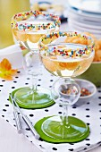 Champagne with melon balls in cocktail glasses decorated with sugar sprinkles on rims