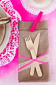 Linen napkin and wooden cutlery on place mat sprayed hot pink through doily stencils