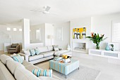 Ecru sofa set and ottoman in spacious lounge in open-plan, white interior
