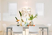 White chairs and various vases of bird-of-paradise flowers and palm fronds in brightly-lit dining area
