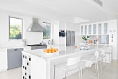 White glossy counter, bar stools and stainless steel fitted appliances in designer kitchen
