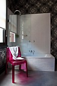 Pink plastic chairs in front of bathtub with glass screen in bathroom with pattern of circles and stars