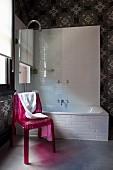 Pinkfarbener Kunststoff-Stuhl vor Badewanne mit Glas-Trennwand, an Wand Tapete mit sphärischem Sternenmuster