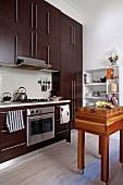 Modern fitted kitchen with dark cupboards opposite butchers' block on castors