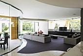 Grossräumiges, modernes Wohnzimmer, kubische Sofagarnitur auf Teppichboden mit geschwungenen Formen, seitlich gebogene Glas Trennwand