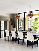 Elegante Esszimmerstühle in Weiss und Schwarz um lange Tafel vor raumhohem Fenster, Bauhaus Pendelleuchten