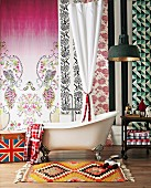Bathroom arrangement - ethnic rug in front of vintage bathroom and wall covered in sections of different patterned wallpapers