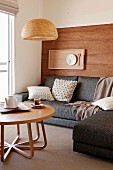 Pale wooden coffee table, grey corner sofa and place setting on tray hung on wooden wall in comfortable seating area
