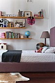 Books and ornaments on wall-mounted shelves above teenager's upholstered bed