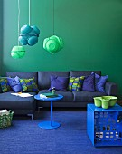 Blue and green colour scheme - blue sofa with scatter cushions against green wall, pendant lamps made from painted colanders and green bowl on blue stool