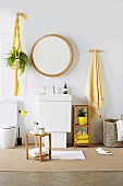 Round mirror above washstand, small wooden stool and yellow accessories