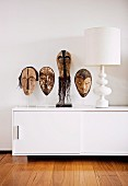 African masks on transparent plastic stand next to white table lamp on designer sideboard