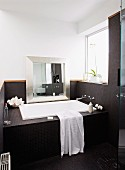 Bathtub in niche built into niche with window, silver-framed mirror leaning against wall, black mosaic tiled on bath surround and walls
