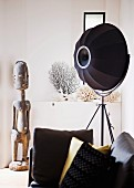 Black studio lamp and African wooden sculpture behind sofa with scatter cushions