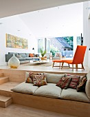 Seat cushions on broad step used as bench in front of modern lounge area on platform with sofa & orange chair