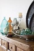 Dish of glass spheres and collection of glass vases on solid wooden cabinet