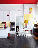 Yellow arc lamp next to dining area with white chairs next to open-plan kitchen area in modern setting