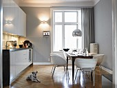 Dog lying on parquet floor in modern kitchen with dining table and chairs