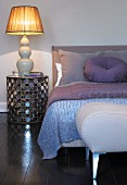 Lilac cushion and bedspread on bed, lamp on bedside cabinet and stool at foot of bed in bedroom