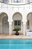 Arcade & pool below circular rack of lamps in courtyard of Moroccan house