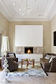 Sofa set and coffee table on rug in front of open fire in elegant ambiance