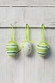 Three painted eggs hanging on white wooden wall