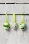Drei bemalte Eier vor weisser Holzwand hängend
