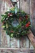 Weihnachtlicher Kranz mit Beeren und Tannenzapfen an Holztür hängend