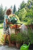 Woman watering flowering plants in sunny garden