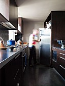 Person in front of fridge in narrow, galley kitchen with two opposite worksurfaces