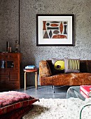 Floor cushion on flokati-style rug and sofa with cowhide cover below framed picture on grey panel wall