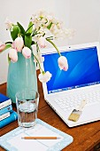 Bouquet of tulips next to laptop and glass of water on rustic wooden table