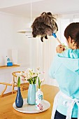 Woman using feather duster to clean pendant lamp above vases of spring flowers on table