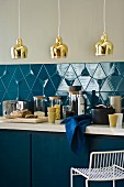 Kitchen counter with blue base units, kitchen utensils in front of blue-tiled splashback & brass pendant lamps