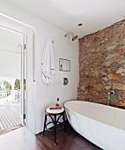 Thonet-Hocker neben moderner freistehender Badewanne vor Natursteinwand und offener Terrassentür
