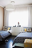 White chest of drawers flanked by twin beds with black and white patterned bedspreads