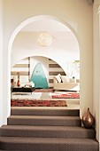 Carpeted steps leading through arched doorway and view into living area with ethnic rugs and modern furnitire