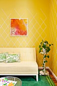 Couch with pale upholstery next to potted plant on plant stand against wall with yellow patterned wallpaper
