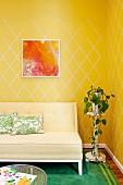 Helle, gepolsterte Sitzbank neben Blumenständer mit Topfpflanze vor Wand mit gelb-gemusterter Tapete