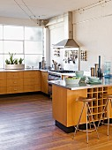 Open-plan kitchen with wooden base units, stainless steel worksurfaces & lighting strung on wires mounted on ceiling