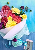 Colourful bouquet of dahlias wrapped in white paper and greetings card on pale blue surface