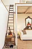Vintage wooden ladder leading to white-painted wooden mezzanine above ecru sofa and ornate, antique mirror on wall