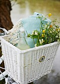 Drink, picnic blanket and bouquet of wild flowers in bicycle basket
