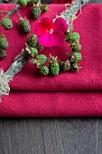 Small wreath of unripe blackberries and geranium flower on bright pink tablecloth
