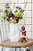 Bouquet of summer flowers in white, retro china vase and figurine of Caribbean girl on wooden table