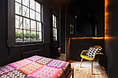 Black-painted bedroom with lattice window, bed with colourful bedspread and retro armchair on plain wooden floor