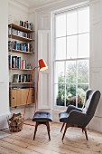 Cosy reading corner next to large lattice window, grey, retro wing-back chair with matching footstool, orange standard lamp and bookcase in niche