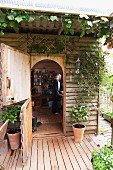 View through open stable door of woman in wooden cabin with encircling, roofed wooden deck