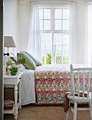 View through open door of double bed at comfortable height with floral bedspread, lattice window and airy curtains
